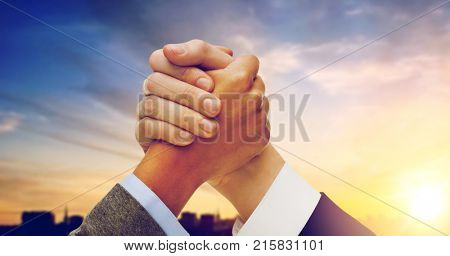 business, confrontation and cooperation concept - businessman and businesswoman arm wrestling over city background