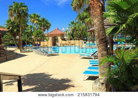 Nice outdoor pool with sun beds. Aruba. Summer background.