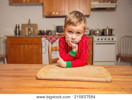 bored little boy sitting in the kitchen at the table. little kid is waiting