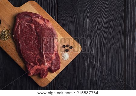 Fresh raw beef meat steaks in the black plate with spices on black wooden background