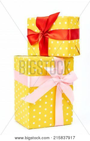 Two yellow dotted gift boxes. Presents are packed in colored paper. Polka-dot pattern tied with a beautiful pink and red ribbons over white background.