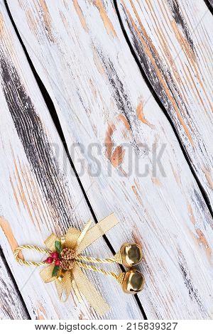 Golden bow with jingle bells, copy space. Golden jingle bells on a rope with a bow on a wooden vintage background, top view. Shiny golden Christmas bells decorations. New Year and Christmas concept.