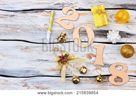Happy new year 2018 alphabet on wooden background. Wood numbers forming the number 2018 for the new year 2018 on white rustic wooden background with Christmas gift and ornaments, copy space.