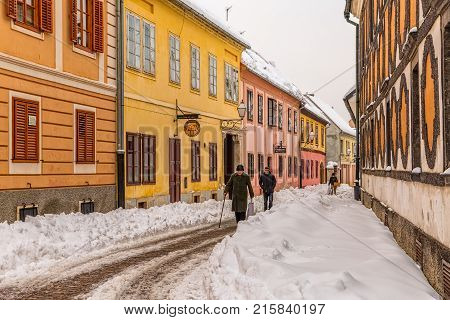 VARAZDIN, CROATIA - FEBRUARY 07, 2015 People walking on the slippery narrow street at the old city center in winter time.