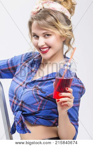 Youth Lifestyle Concepts. Extremely Surprised Caucasian Blond Woman in Checked Shirt Drinking Red Juice Using Straw. Posing On White.Vertical Image Composition