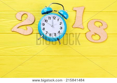 Number 2018 from wood and alarm clock. New year 2018, clock counting down, yellow wooden background, copy space. Happy New Year. New Year 2018 concept.