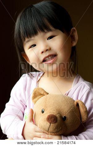 Niño sonriente con un oso de peluche