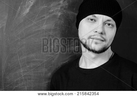 young bearded attractive man in black with a confident look on the background of a school board. black and white.