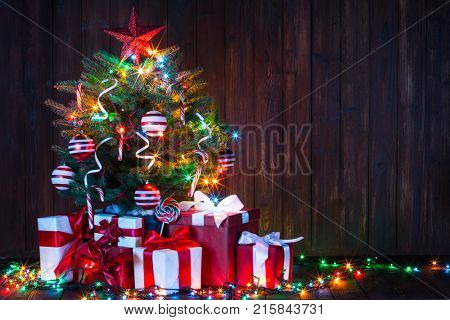 Decorated Christmas tree with glowing lights and gift boxes on wooden background