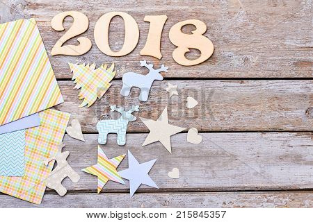 Wooden text 2018 and New Year paper figures. New Year handmade design on old vintage style wooden background. New Year 2018 decorations and copy space, rustic wooden background.