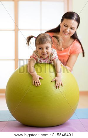 Woman with happy child doing exercises with gymnastic ball at fitness class. Concept of caring for the baby's health.
