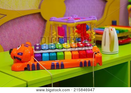 Rainbow colored xylophone on the table among toys in baby room.