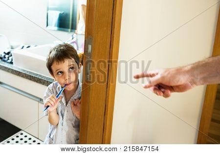 Naughty boy brushing his teeth