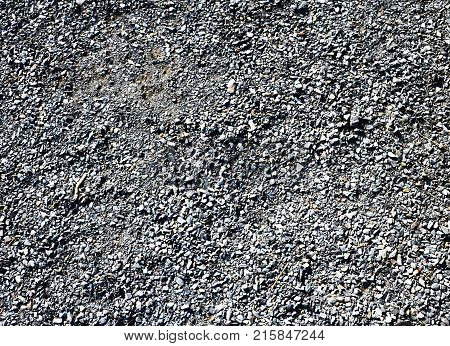 Granite gravel of macadam rock gray crushed for construction on the ground scree texture background.