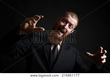Crazy Funny face. Handsome businessman with beard and handlebar mustache looking at camera