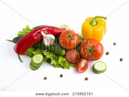 Red peppers and yellow peppers with tomatoes on a white background. Fresh vegetables on a white background. Composition from vegetables. Red and yellow peppers on white background with garlic. Tomato with peppers and cucumber on a white background.