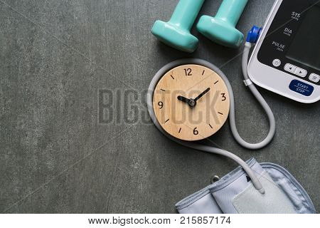 Top view of clock dumbbell and blood pressure monitor on the table background schedule to check up healthy concept