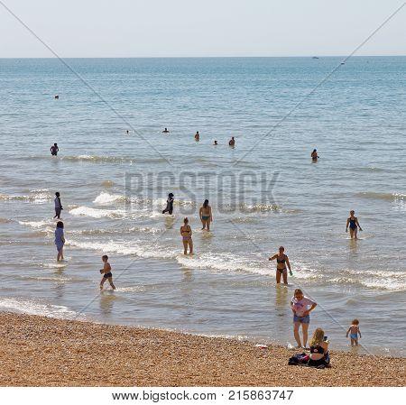 BRIGHTON GREAT BRITAIN - JUN 17 2017: Sunbathing people on the Brighton beach West pier in the background. June 17 2017 in Brighton Great Britain