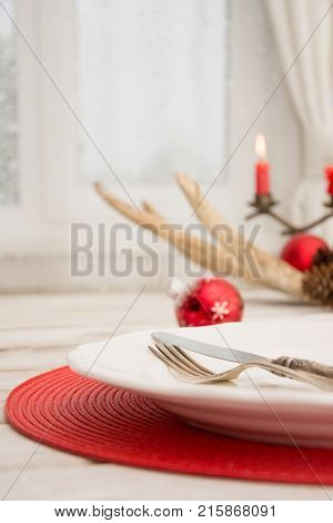 Christmas Place Setting With White Dishware, Silverware And Red Decorations On White Board In Interi