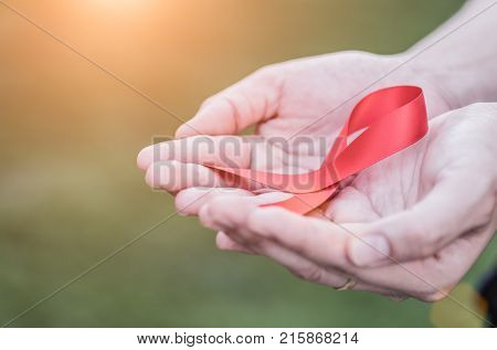 Female hands holding red AIDS awareness ribbon. Aids Awareness campaign.