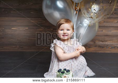 Portrait Of Cute Adorable Baby Girl Celebrating Her First Birthday With Cake And Balloons