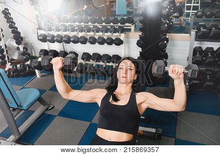 Young Athletic Woman Training Hard With Dumbells At Gym