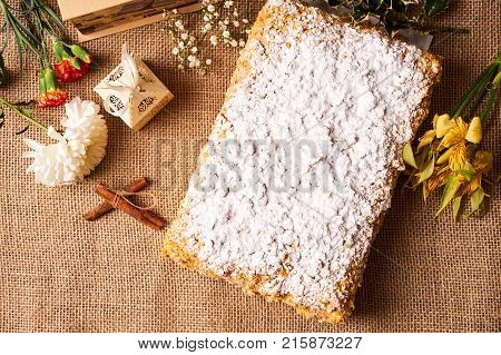 Napoleon cake. Layered puff pastry napoleon cake with powdered sugar and butterscotch frosting on sackcloth decoration background, top view. Sweet dessert food