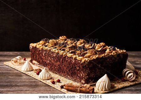 Delicious Chocolate cake with walnut and  whipped custard sour cream on cake board with decorations, close-up. Sweet dessert food