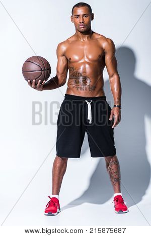 full length view of athletic shirtless african american man with basketball ball looking at camera on grey