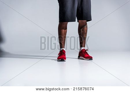 low section of african american man in sports shoes on grey
