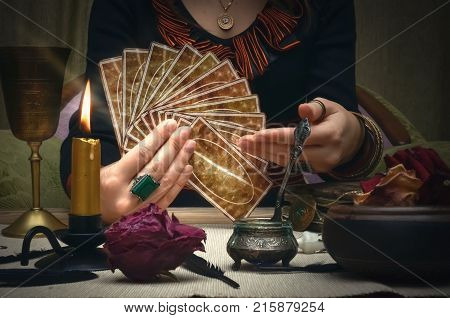 Tarot cards. Future reading. Woman fortune teller holding in hands a deck of tarot cards and shows on it.