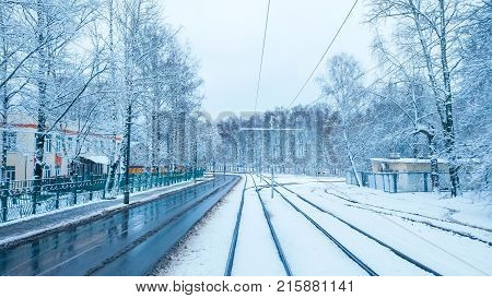 White snow city on a tramway in November, first snow in December. Snow-covered city with trees in winter. Rails sleepers turning into distance.