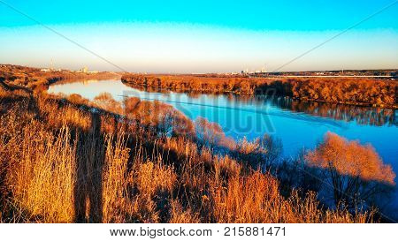 Beautiful scenery of the Oka river in Kolomna, autumn panorama, bright autumn in November. Golden trees, blue sky. Bright reflection of trees in the river. The lake goes into the distance.