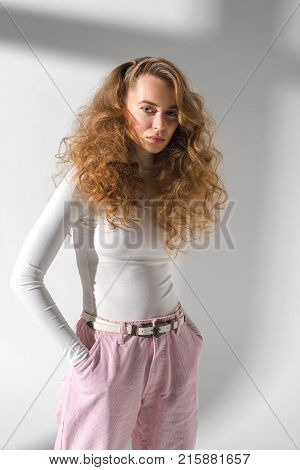 confident stylish girl with curly hair standing with hands in pockets and looking at camera