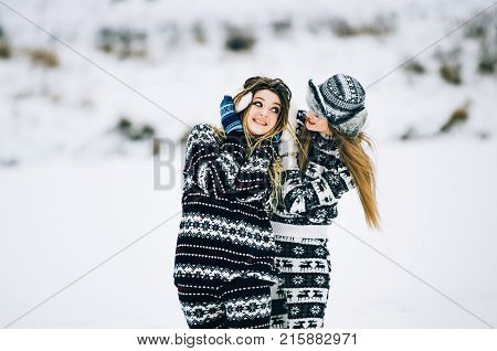 Couple of young woman. Girl wears warm hat girl closes friend's ears with her hands in mittens in cold winter