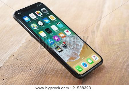 Koszalin, Poland - November 29, 2016: Space gray iPhone X on wooden table. The iPhone X is smart phone with multi touch screen produced by Apple Computer, Inc.