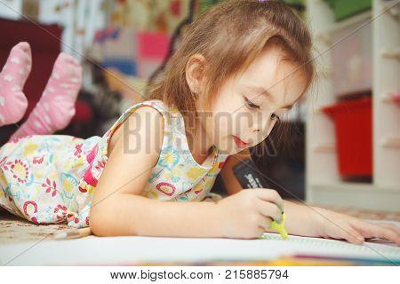 Pretty little girl carefully draws picture in notebook with bright felt pen and lies on floor concentrated on work. Adorable child occupied with creative hobby.