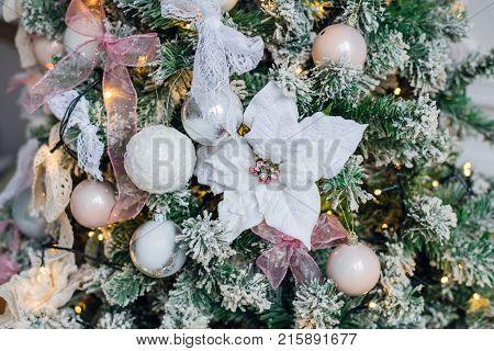 Embellished Christmas tree decoration white flower close-up.