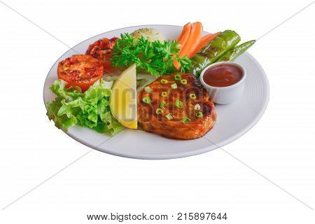 White isolated background with clipping paths homemade pork steak or barbecue. Delicious pork steak on white plate served with mash potato, barbecue sauce and vegetable. Delicious food for lunch or dinner. Pork barbecue or steak ready to serve.