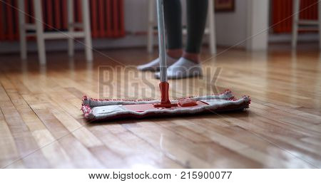 Woman using mop cleaner to do household chores faster and tidy home