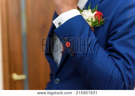groom in a jacket, boutonniere on a jacket, the groom adjusts his jacket, The morning of the groom, business style, man in a jacket.