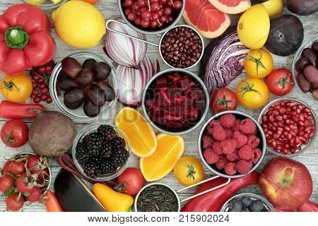Healthy eating super food with health promoting properties with fruit, vegetables, pulses and grains very high in anthocyanins, antioxidants, minerals and vitamins on rustic wood background. Top view.