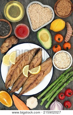 Food to benefit a healthy heart concept with mackerel, vegetables, fruit, tomato juice, spice, seeds, olive oil, cereal and grain. Foods high in antioxidants, vitamins and omega 3 fatty acids.