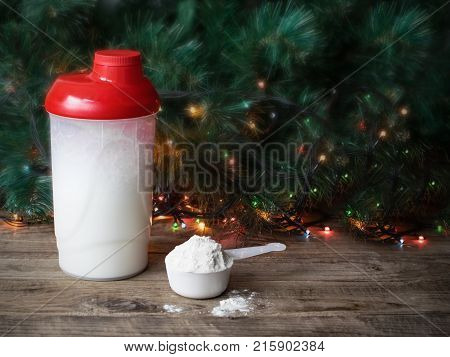 Whey protein glass and scoop on christmas background. Sports nutrition