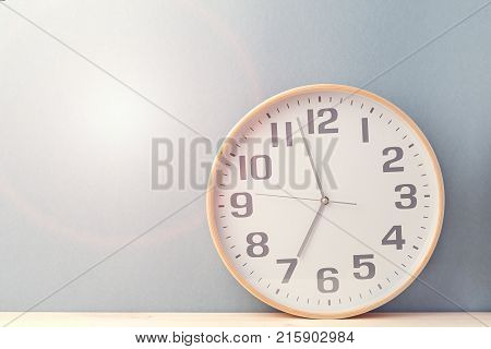 Simple round clock showing time while composed on wood against blue.