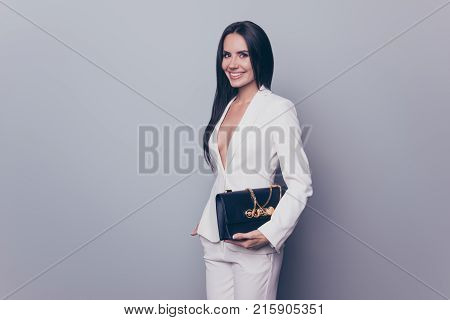 Portrait of confident funky wealthy beautiful gorgeous cute business lady with toothy beaming smile she is wearing white smart suit and holding black handbag isolated on grey background copyspace poster