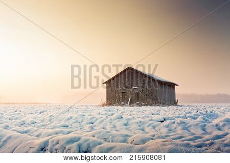 The risin sun colors the snowy fields amber. A lonely barn house stands on the empty winter fields at the Northern Finland.