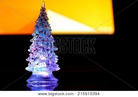 A small lighting Christmas tree on the contrast dark and orange geometric background. Selective focus reflections geometric lines. Abstract colorful Christmas background.