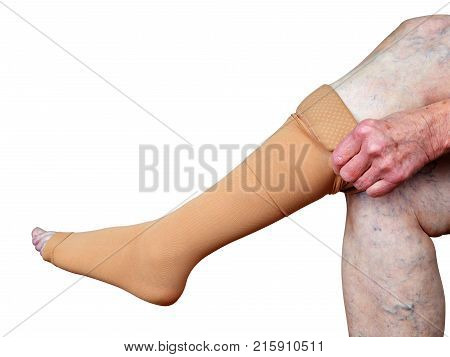 Thrombosis stockings on a leg of old woman isolated on white background.
