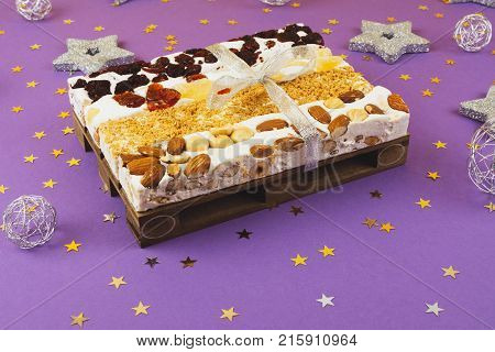 Traditional italian festive torrone or nougat with nuts on lilac background.